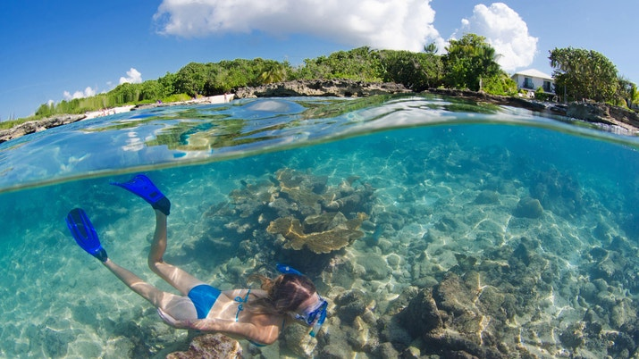 Over under photo of snorkeler in blue at smith cove