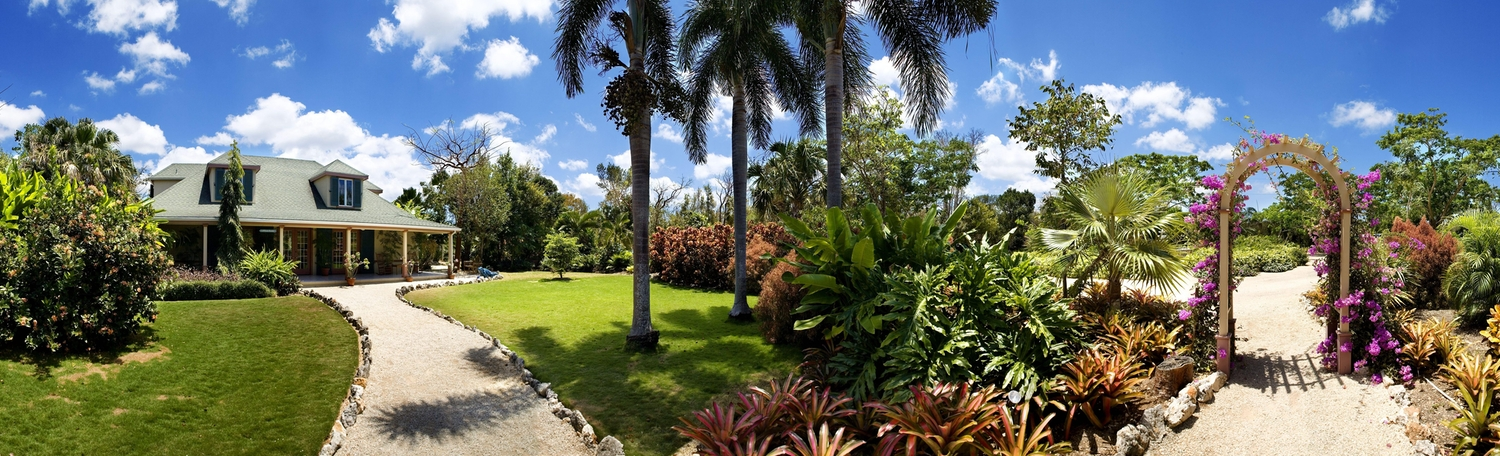 Panoramic view of a beautiful house with front yard garden and arch