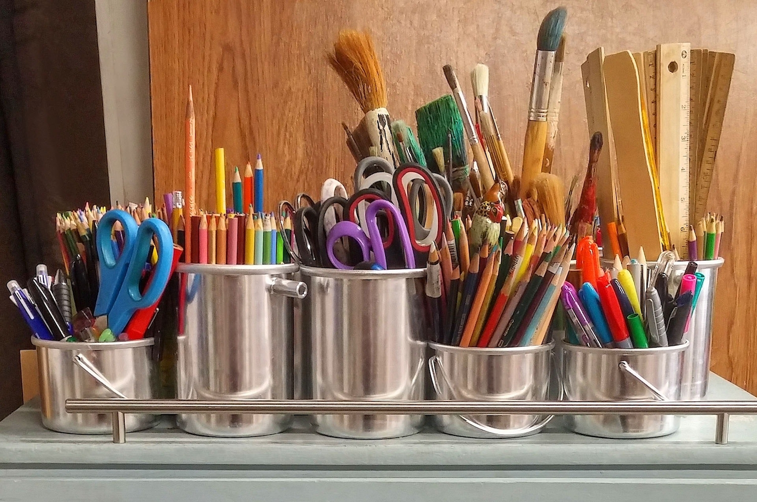 Pencils and paint brushes in stainless steel bucket