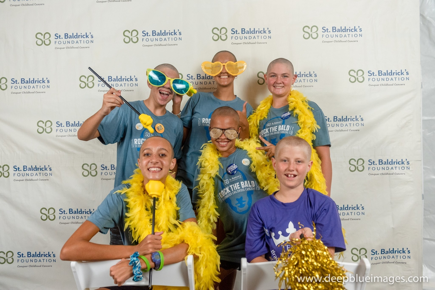 People who did the Big Shave Fundraiser for the St Baldricks foundation in front of a screen