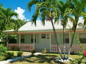 Quaint mint green traditional cayman cottage with veranda and pink blossom trees