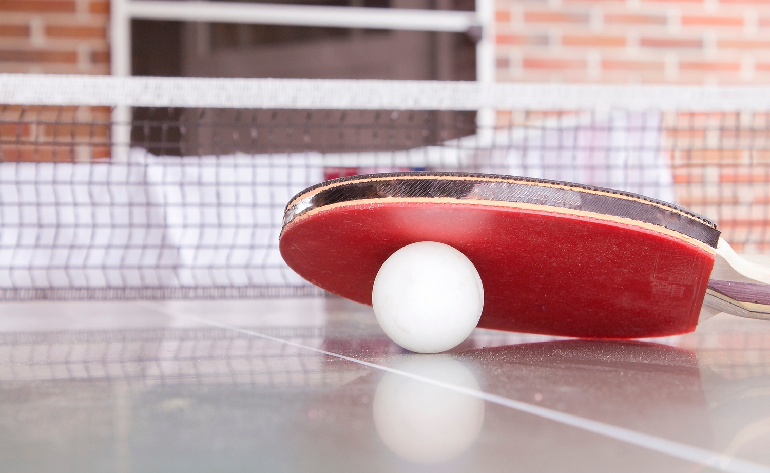 Red racquet resting on a white ping pong ball