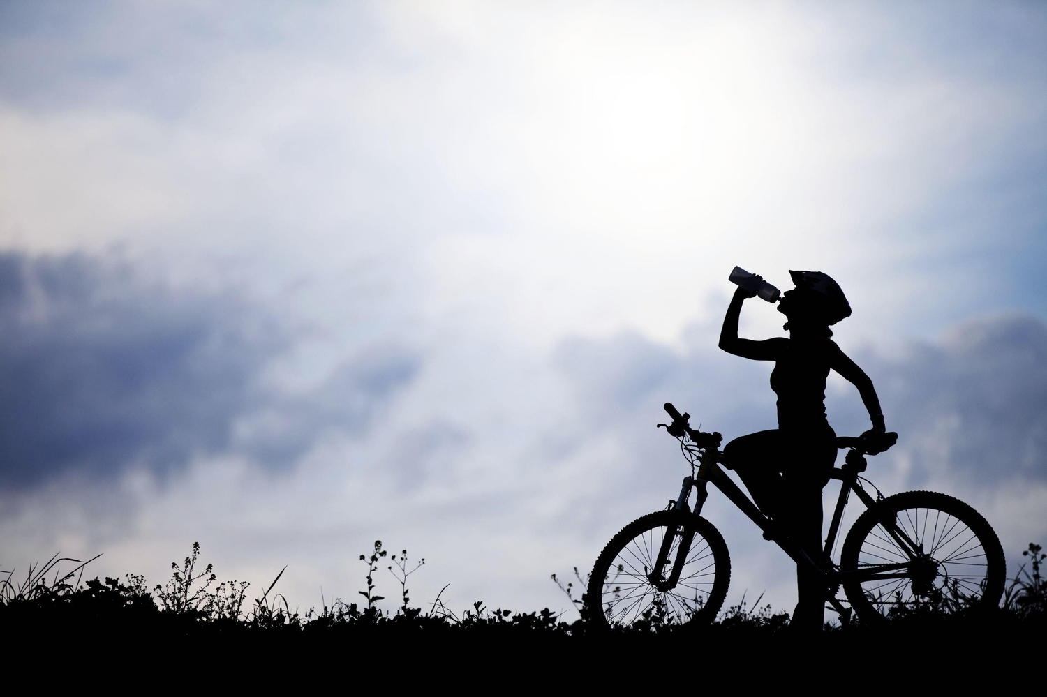 Silhouetted woman drinking water on a bike