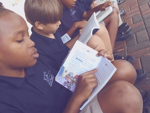 Students at First Baptist Christian School sitting on a curb reading