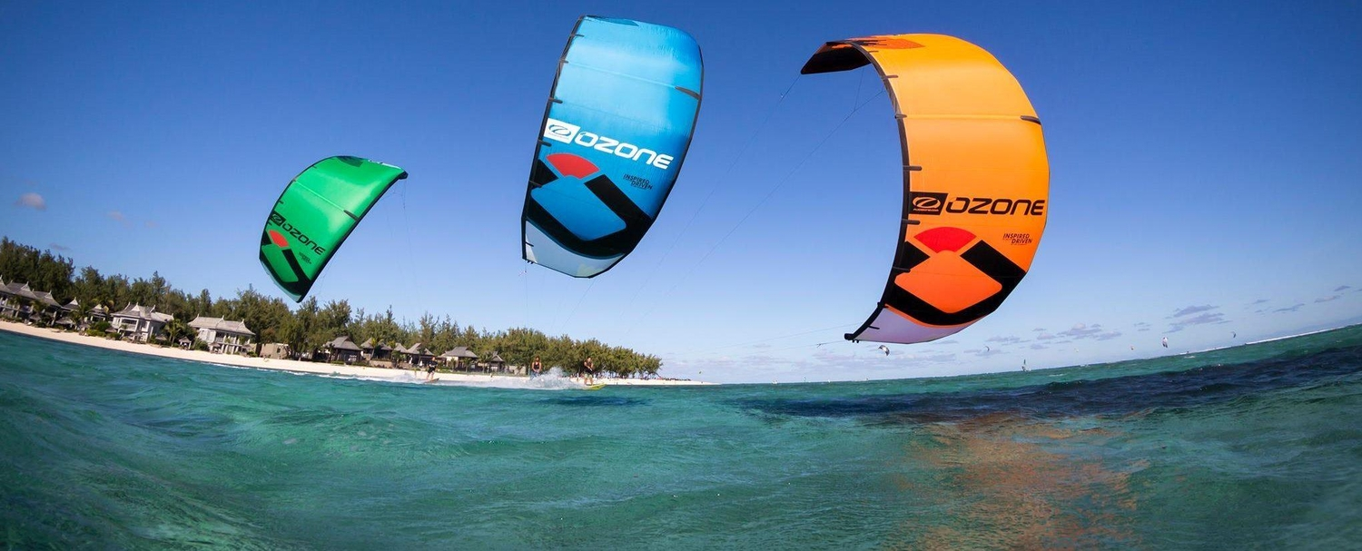 Three bright kitesurf sails close up with shoreline in the background