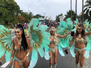 Three girls in carnival wear walking down west bay road