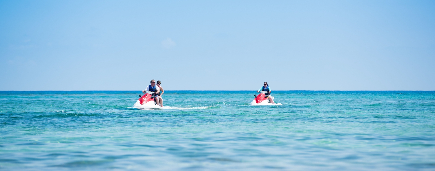 Three people enjoying the afternoon jetskiing on the beautiful blue ocean