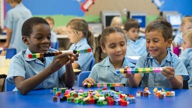 Three school age children playing with blocks