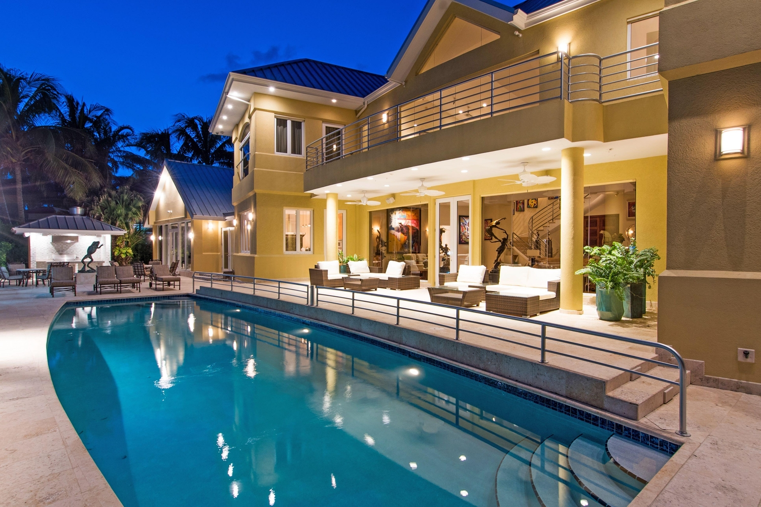 Twilight view of a lit pool and deck