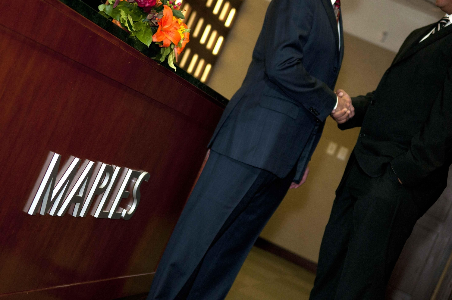 Two businessmen shaking hands outside the maples office