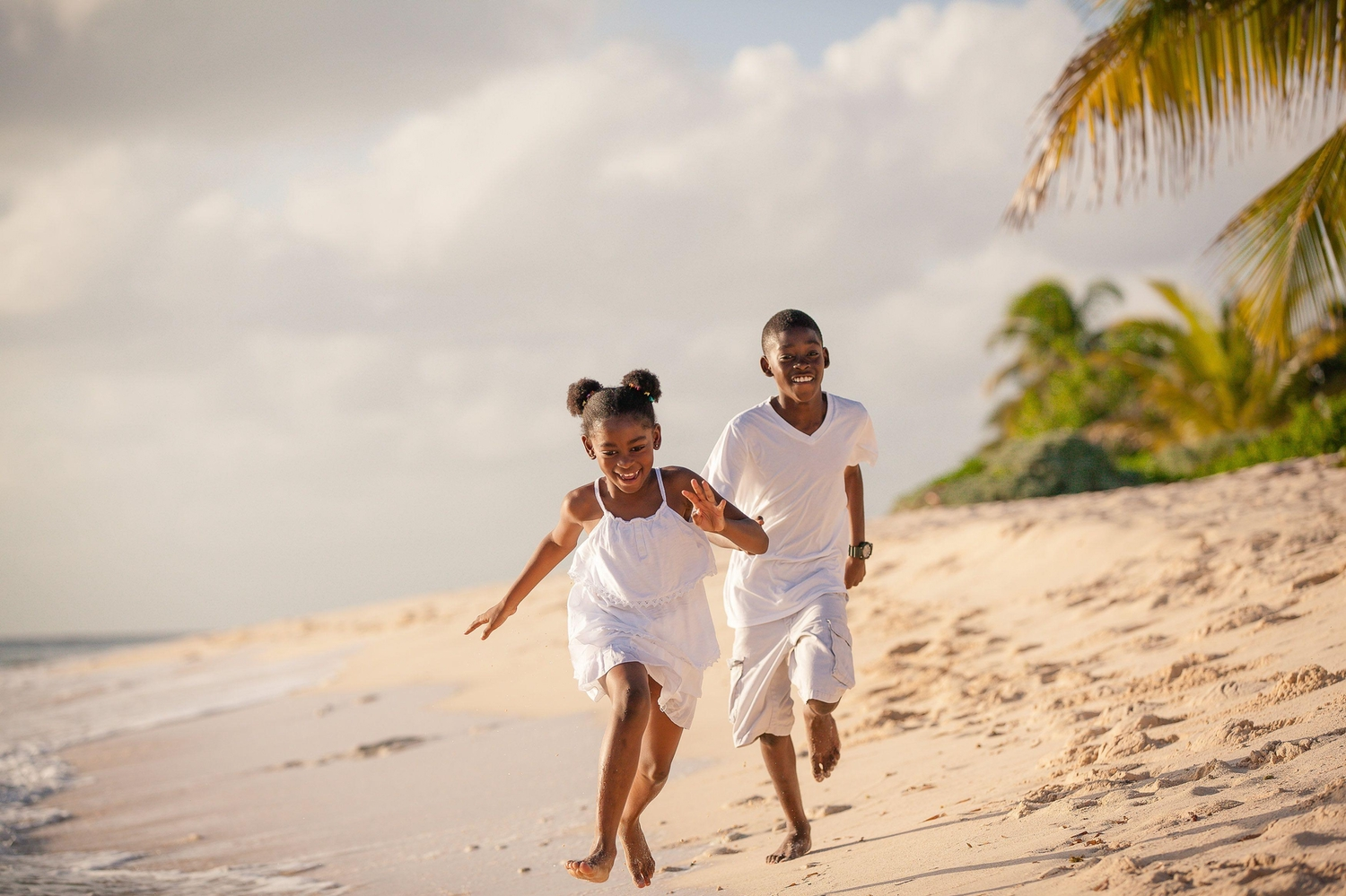 Two children running down the beach laughing