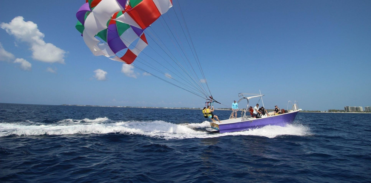 Two people starting to lift off parasailing behind a boat
