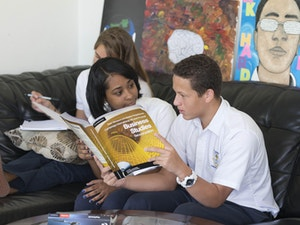 Two students reviewing a manual for college