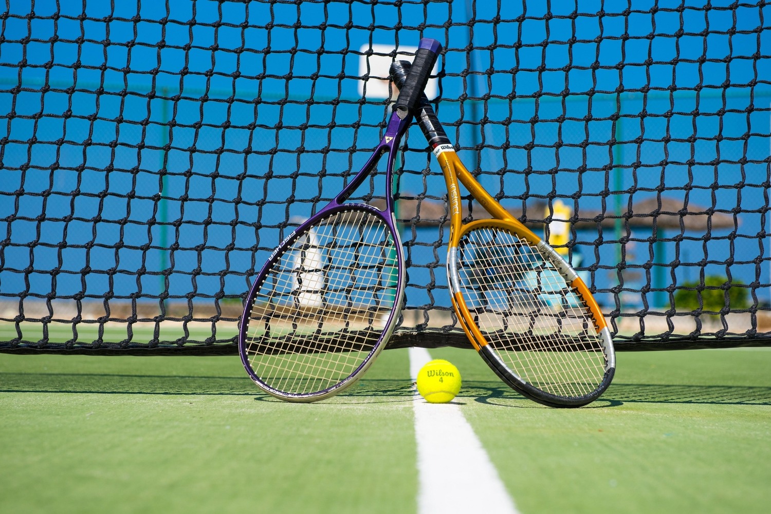 Two tennis racquets leaned up against a net with a ball