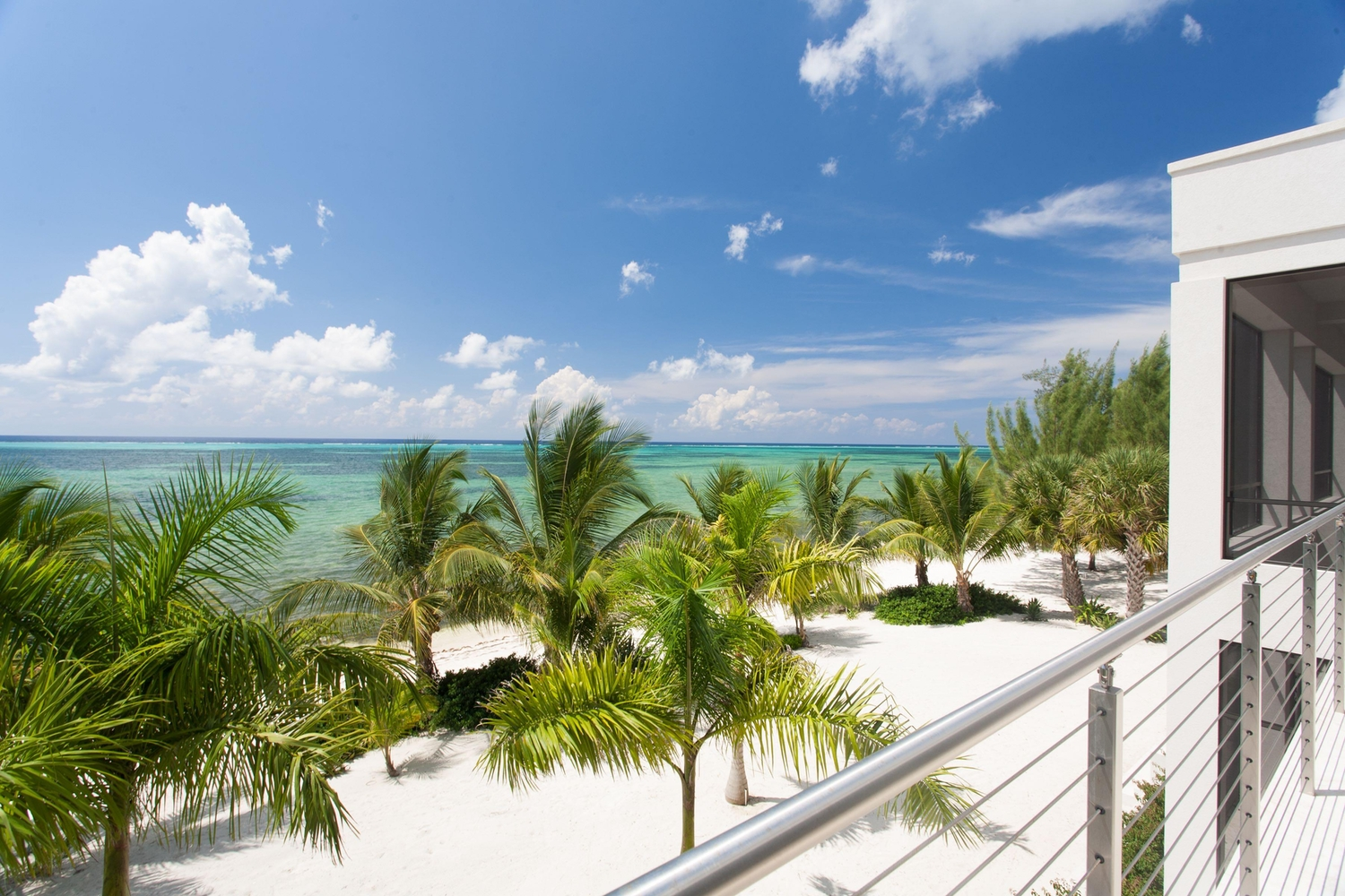 View off of a white luxury condo balcony overlooking the ocean
