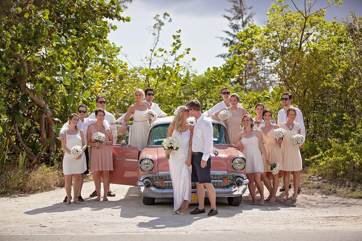 Wedding party sitting in front of pink classic car