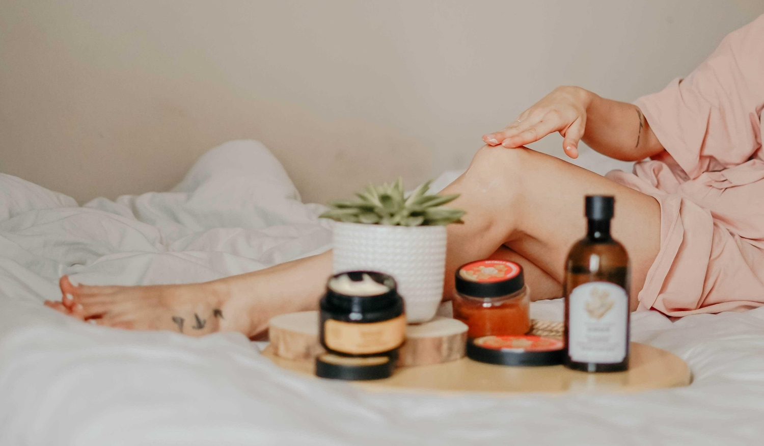 Woman with holistic beauty products lounging on a bed with only leg visable
