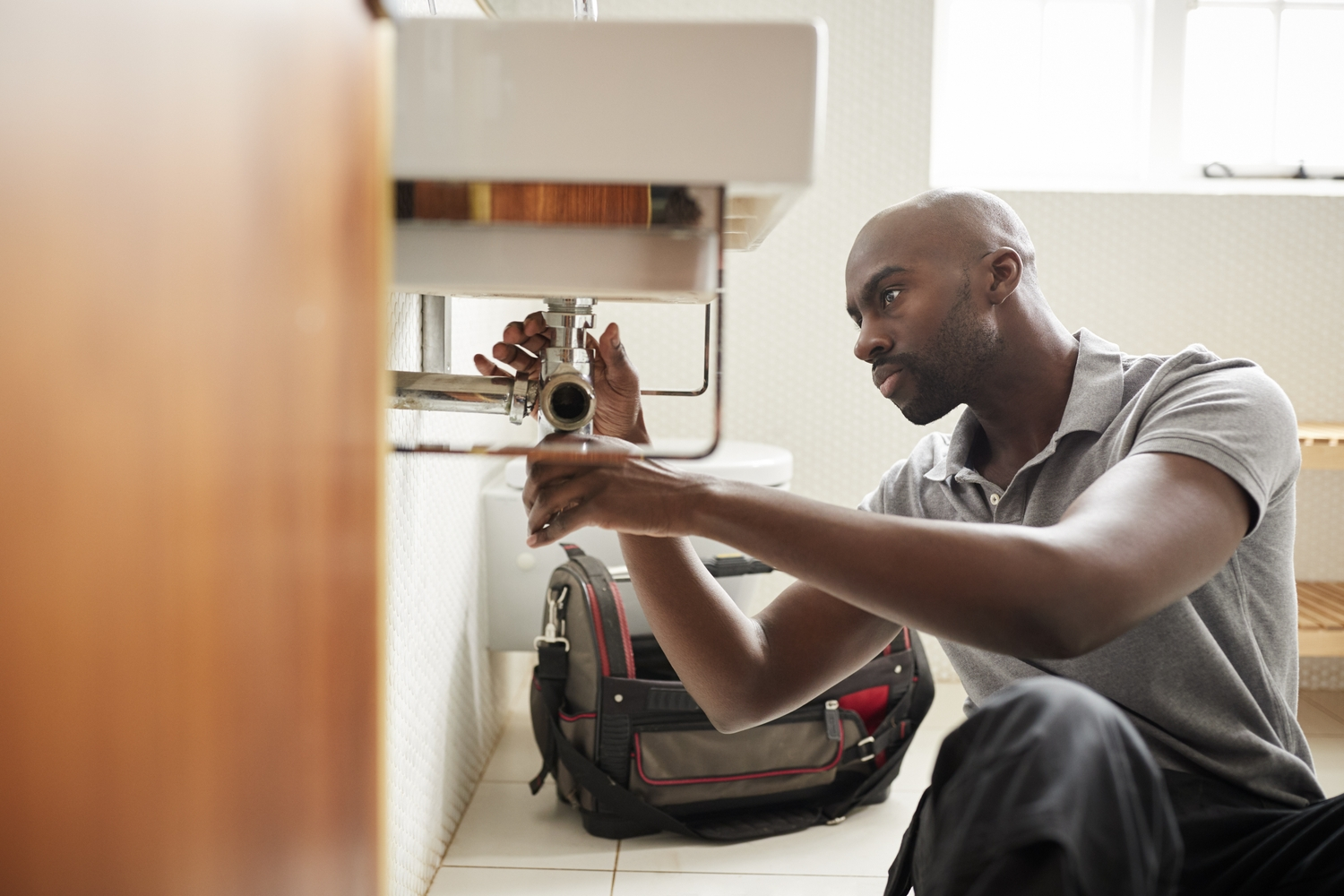 Young black male plumber fixing under sink